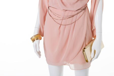 Detail of a beautiful delicate dress with gold accessories. Golden clutch bag with belt and bracelets.