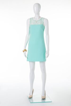 Gently turquoise dress on elegant mannequin. Mannequin in festive dress and beige high-heeled shoes. Stock Photo