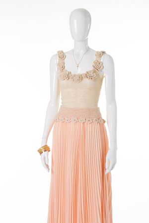 Beautiful delicate womens clothing on a mannequin. Gently peach chiffon skirt made and beige knit tank top.