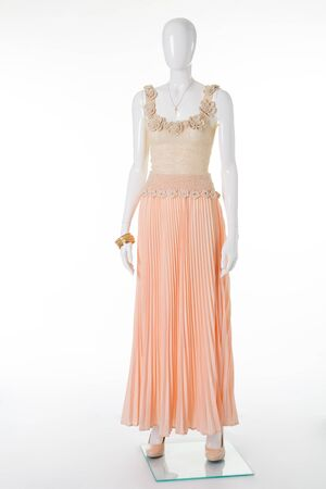 Beautiful elegant summer outfit on a white mannequin. Knitted top and chiffon pleated skirt.