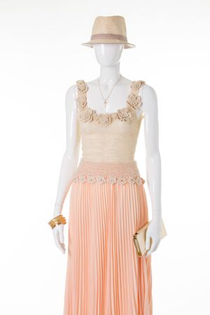 Beautiful summer dress on a white mannequin. Mannequin wearing a straw hat and a light dress.