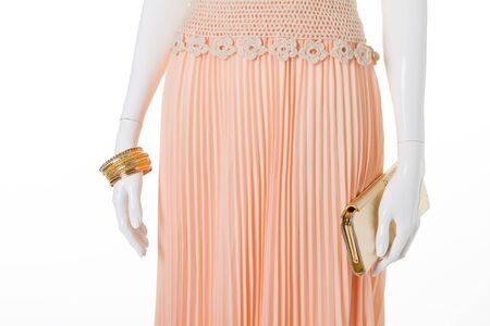 Beautiful pink skirt with a gold clutch and bracelets. Detail of female attire.