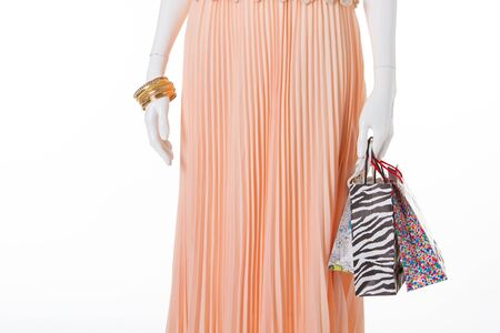 Peach skirt and shopping bags on a mannequin.Summer shopping and discounts.