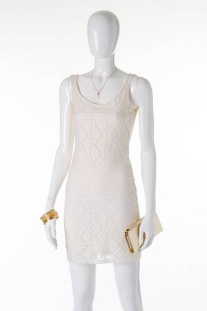 Mannequin in a white lace dress. Gold pendant, bracelets and a clutch on a white mannequin.