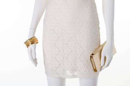 Handbag and accessories on mannequin. Female mannequin wearing wrist accessories. Golden bracelets and purse.