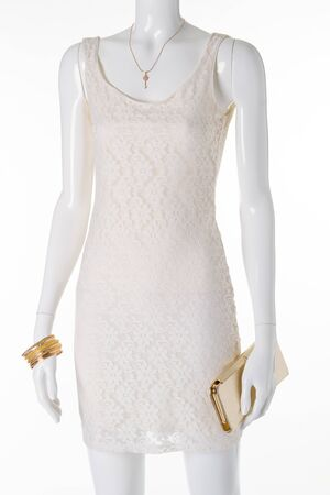 Mannequin in a white openwork lace dress. Gold pendant, bracelets and clutch on a white mannequin. Stock Photo