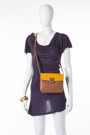 Beautiful stylish dress with a purse on a white mannequin. Mannequin for showcase the new clothing store. Stock Photo