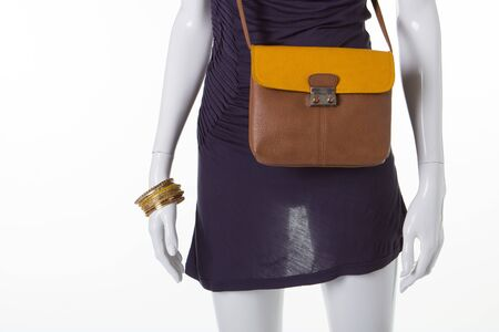 Brownish-yellow leather bag on a mannequin. Mannequin in a dark dress and a leather purse. Reklamní fotografie