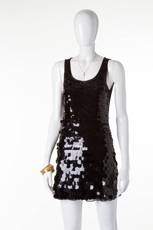 Shiny black dress with sequins on a white mannequin. Beautiful evening dress for the holiday.