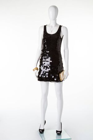 Black disco dress in sequins on a white mannequin. Little black dress with black shoes and a gold purse.