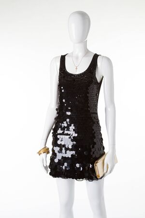 Beautiful evening dress with golden purse for the holiday. Shiny black dress with sequins on a white mannequin.