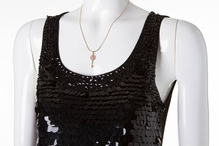 Gold chain with a key on a white mannequin. Elegant black dress in sequins on manikene. Stock Photo