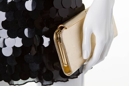 Detail of evening dress. Golden clutch and black dress in sequins.