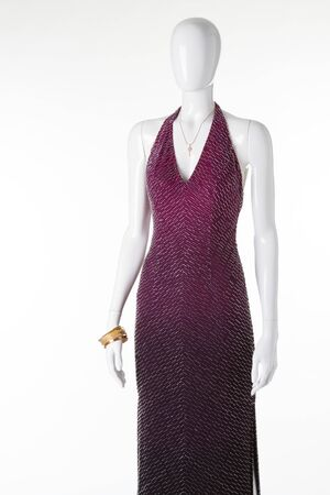 Elegant evening dress with gold accessories. Glittering dress on a mannequin.