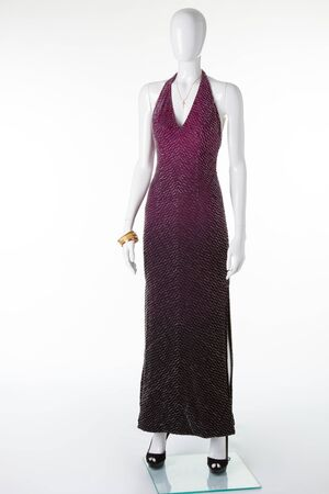Long evening dress embroidered with beads on a white mannequin. Evening dress for party and ceremonies.