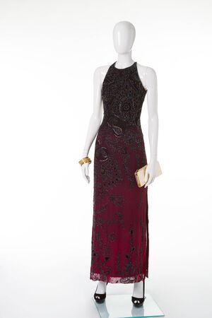 Long dark maroon dress with patterns on the shop window. Evening dress white mannequin.