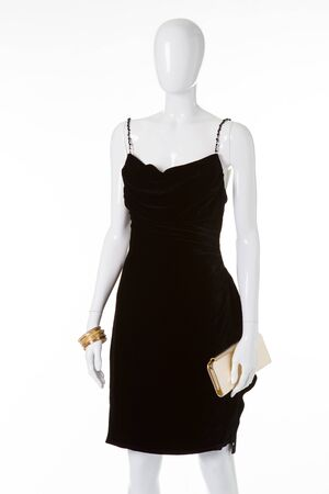 Black velvet dress on white mannequin. Showcase of female store. Gold accessories with a black dress.