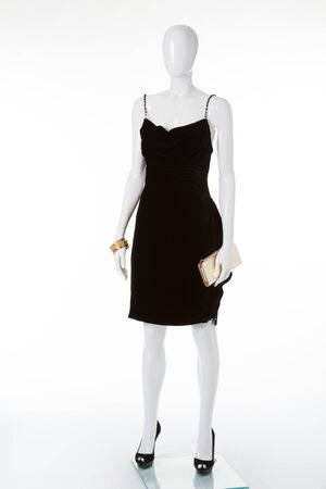 Exclusive black dress on a white mannequin. The classic black dress. Evening cocktail dresses.