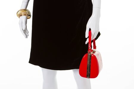 Fashion red bag in the hand of mannequin. Black classical dress and red handbag.