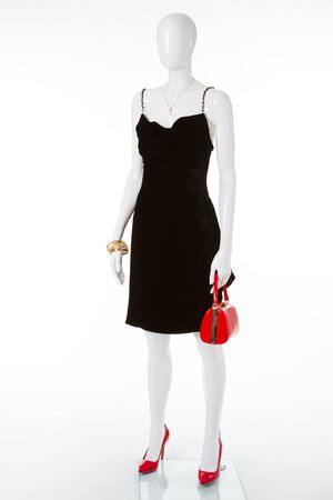 Beautiful black velvet dress with a white mannequin. Red bag and shoes complement the black dress.