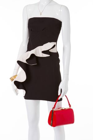 Cocktail black dress with red handbag. Beautiful mannequin for shop window.