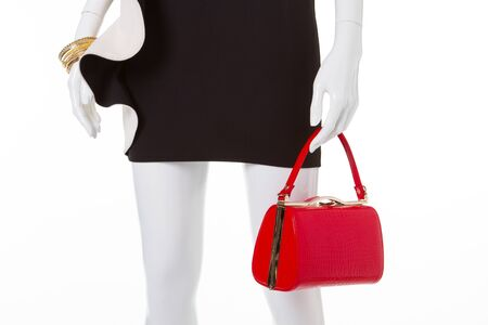 Fashion black dress with white basque. Cocktail dress with red handbag.