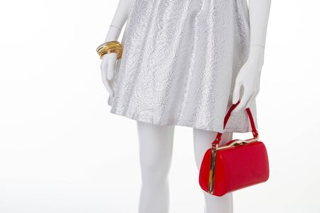 Fashion light dress and red bag. Dressy mannequin on advertising a store.