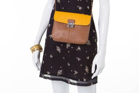 Beautiful summer dress with an unusual print. Yellow brown clutch on a mannequin. Stock Photo