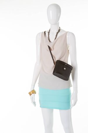 Beautiful summer light suit on a mannequin. Beige blouse and turquoise skirt with a black clutch on a white manikene.