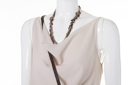 Beige blouse with metal necklace. Stylish accessory on mannequins neck. Ladys exclusive jewelry. Colorful garment and expensive necklace.