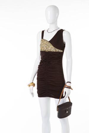 Elegant black dress with rhinestones and retro bag on white manikene. Evening dress for a cocktail party.