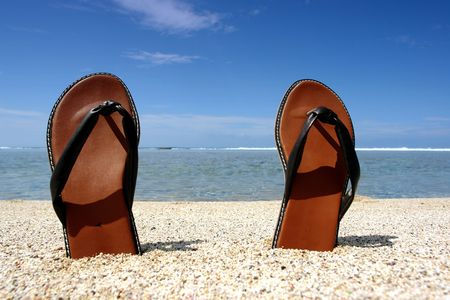 pair of sandals of beach, summer holidays on a white sand beach tropical, photo