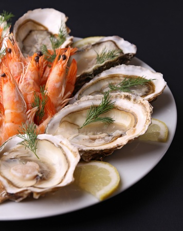 marine crustaceans: plate of oyster and shrimp on black