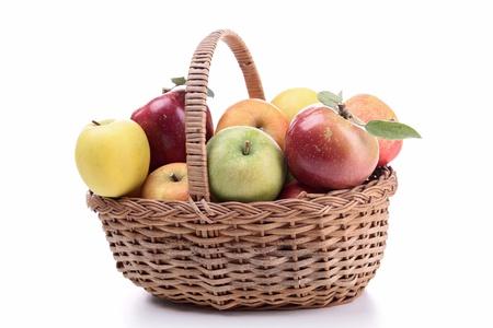 cesta de frutas: cesta de mimbre aislada con manzanas Foto de archivo