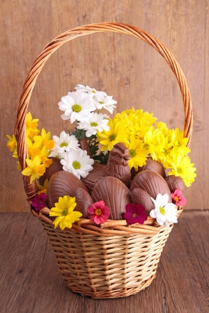 easter eggs in wicker basket with flowers photo