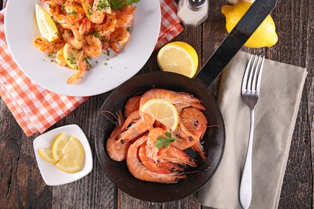 pan: fried shrimps with parsley and ingredient on table