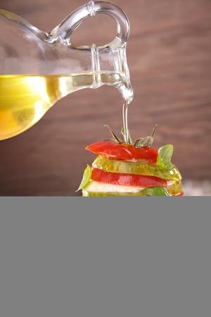 onto: Pouring oil onto tomato, mozzarella and basil