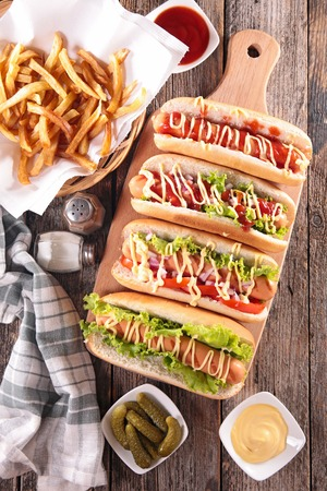 hot dog: hot dog on board with sauce and french fries