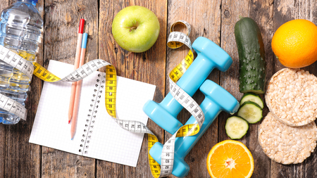 healthy foods: diet food concept with dumbbell,apple and meter