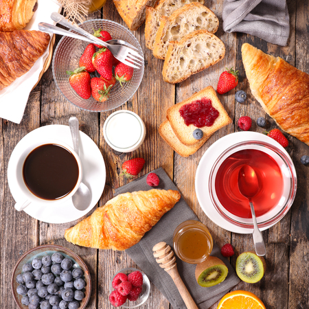 breakfast composition with coffee, tea, croissant and fruit