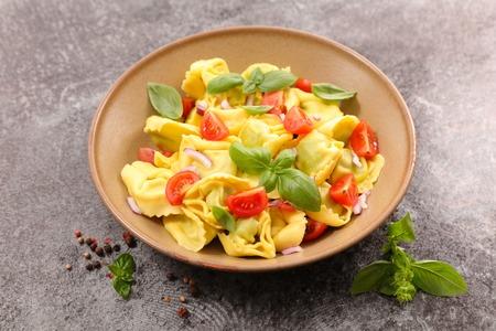 tortellini: tortellini with tomato and basil Stock Photo