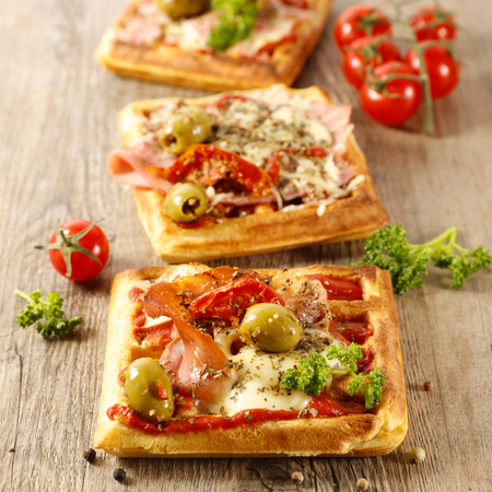 Waffle pizza with tomato, ham and olive Stockfoto