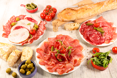 assorted salami, bacon and ham with bread and olive