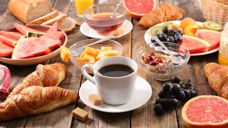 breakfast with coffee cup, tea cup, croissant and fruit