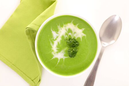 bowl of green soup and cream, top view