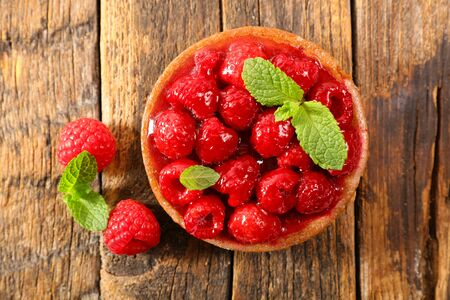 raspberry tart on wood background, top view