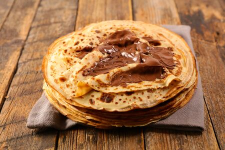 crepe with chocolate on wood background