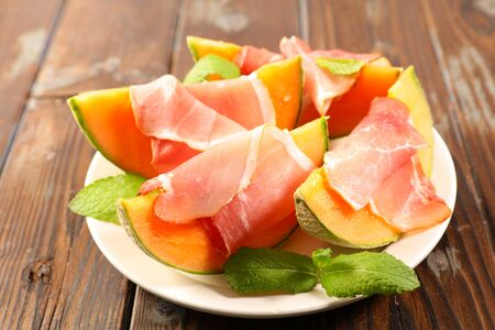 plate of melon slice with prosciutto ham and basil