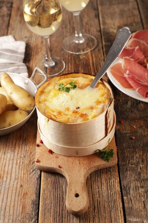 traditional french dish- cheese fondue with bacon, salami and potato- mont dor