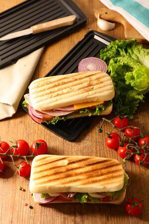 panini, sandwich bread with tomato, lettuce, onion, ham and cheese